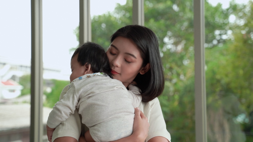 Young Asian mother stands holding a child. To lull him to sleep in the living room of the house  | Shutterstock HD Video #1061235940