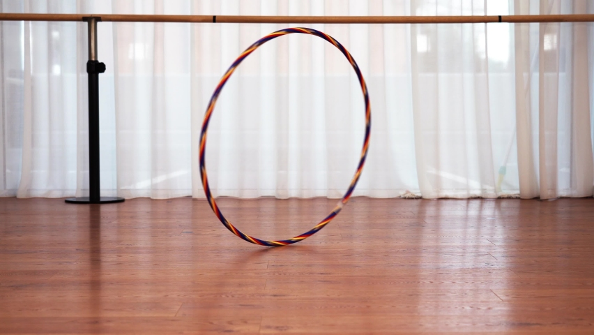 Large colourful hula hoop spins falls down on brown floor | Shutterstock HD Video #1061239435