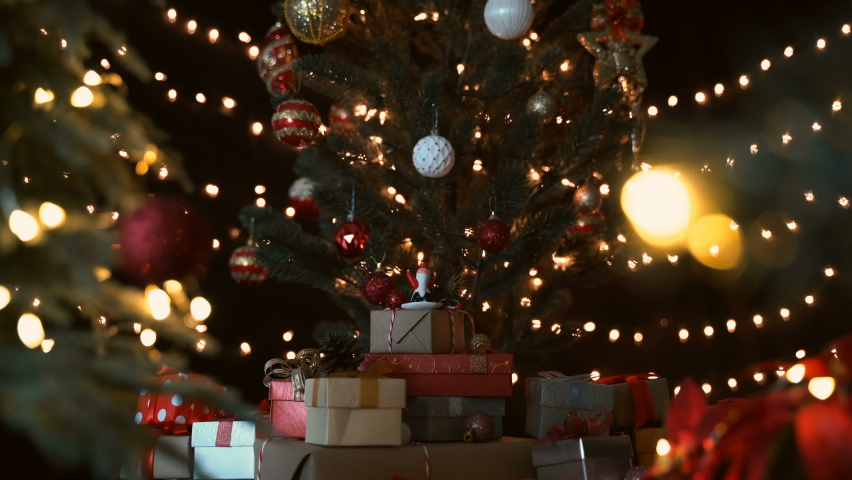 Santa claus figurine with stack of gift boxes under a beautiful decorated christmas tree against bokeh lights at night. | Shutterstock HD Video #1061240749