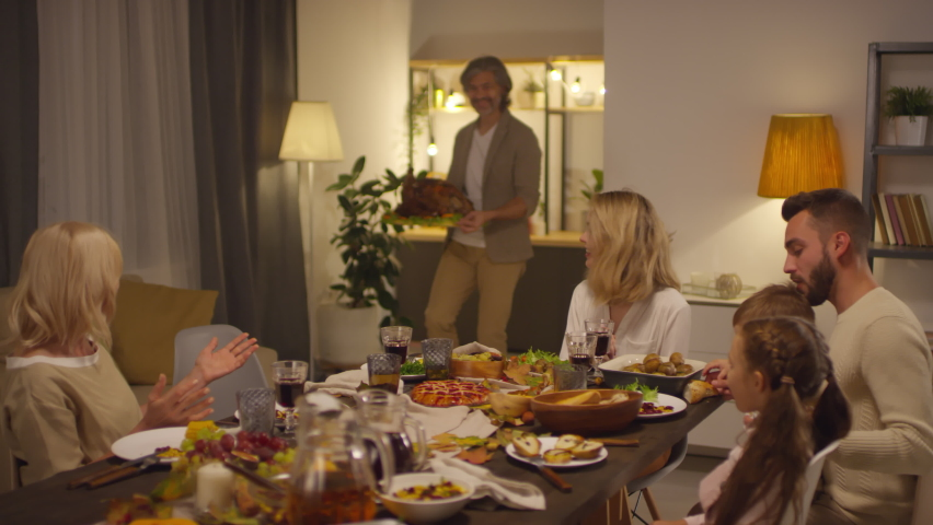 Stylish mature man bringing big roasted turkey to Thanksgiving day dinner, his cheerful family clapping hands, slow motion shot footage | Shutterstock HD Video #1061241334