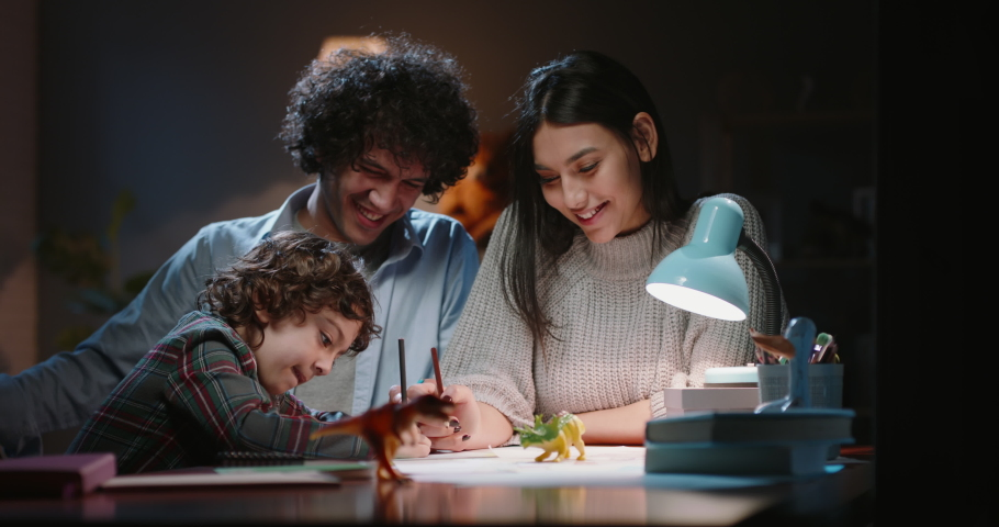 Happy asian family spending time at home togther. Young parents teaching their little kid with curly hair how to draw, having fun - happy family, togetherness concept 4k footage | Shutterstock HD Video #1061242699