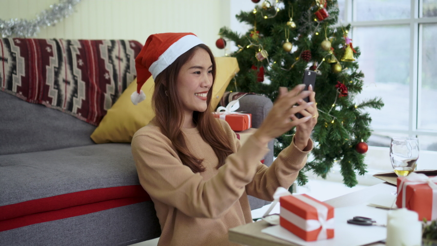 shot on young asian woman holding smartphone to video call (facetime) with family and friends in living room at home to greeting merry xmas and happy new year for seasonal festival concept Royalty-Free Stock Footage #1061243263