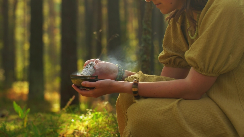 Occult science and supernatural concept - young woman or witch with smoking white sage performing magic ritual in forest | Shutterstock HD Video #1061244136