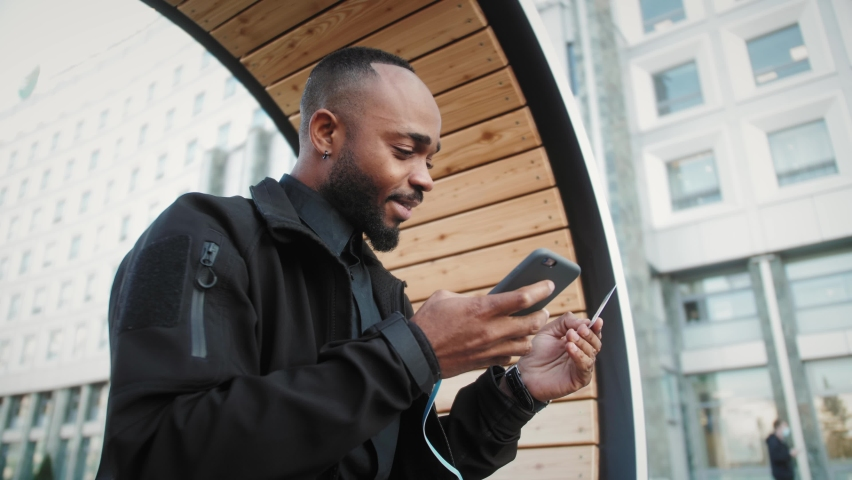 Student on street with credit card and phone Black man sitting on the bench and makes online payments via Internet Royalty-Free Stock Footage #1061246506