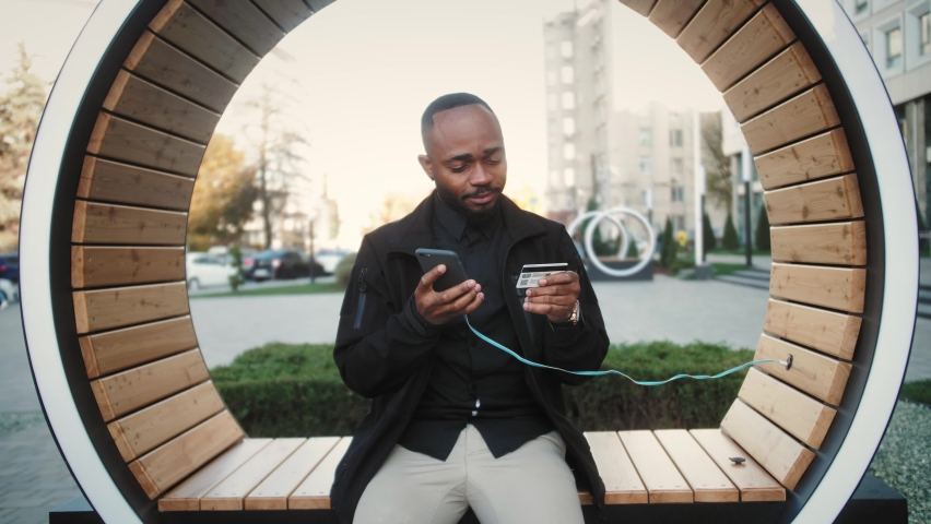 Student on street with credit card and phone Black man sitting on the bench and makes online payments via Internet Royalty-Free Stock Footage #1061246512