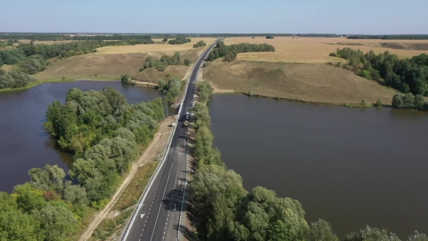 Route and bridge over the river. Modern track. Panorama and beautiful view. Copter. Low traffic | Shutterstock HD Video #1061248078
