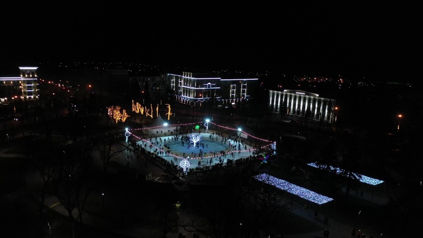New Year's ice skating rink. There are many people at the rink. Night time Christmas lights and decoration in a city park. Aerial view | Shutterstock HD Video #1061249209