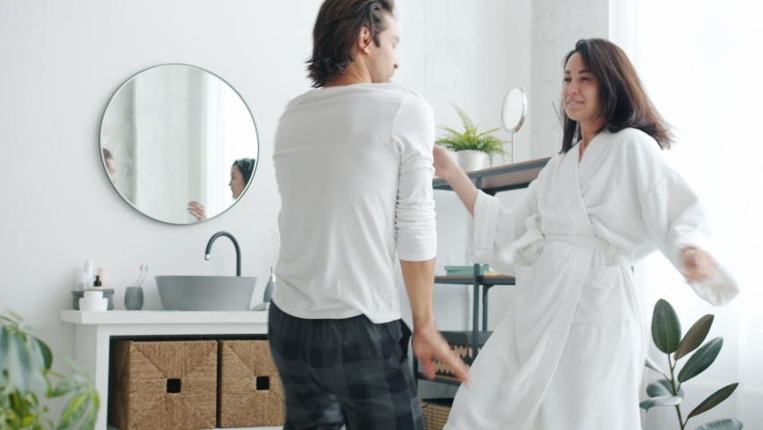 Active youth husband and wife are dancing enjoying music laughing and having fun in modern bathroom. Relationship and leisure time concept. | Shutterstock HD Video #1061250703