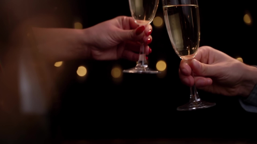 Two people clinking each other's with glass of champagne on black background. Concept holiday, new year, Christmas, birthday | Shutterstock HD Video #1061253202