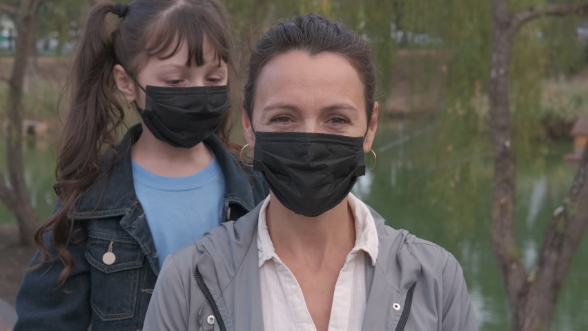 Stay with mother in quarantine. A nice happy child in medical mask hugs her mother in mask by the city pond. | Shutterstock HD Video #1061257048