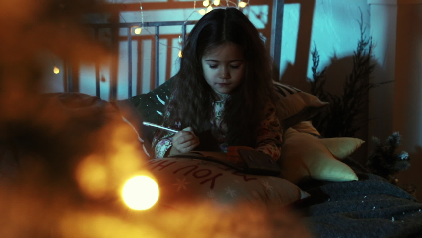 Cute little girl is lying on bed and write letter to Santa near christmas tree and gifts, christmas and new year eve concept