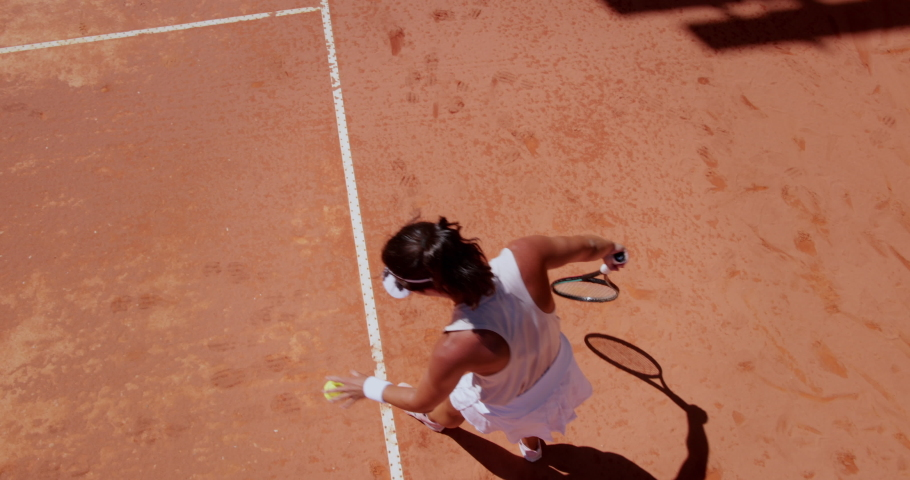 Woman serving ball during tennis match on clay court | Shutterstock HD Video #1061258305