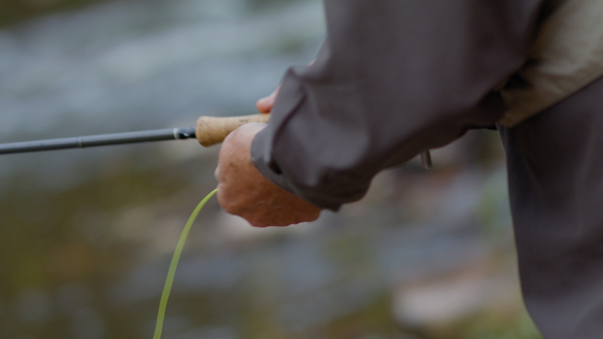 Fly fisherman fishing with spinning Male hands twist the spinning reel fly while fishing.  Fisherman catches fish in slow motion Fly Fishing Reel with river water on background, close up.   Royalty-Free Stock Footage #1061259112