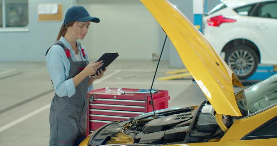 Mechanic using a digital tablet while doing routine maintenance check-up on a car in a garage.