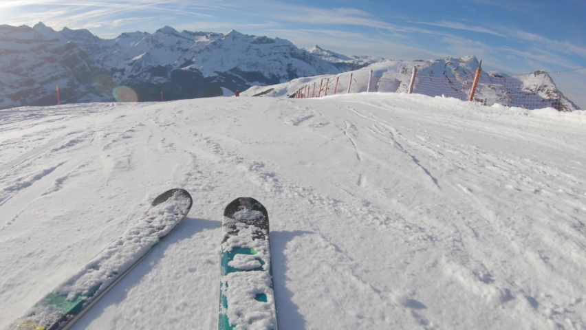 Skiing on snow slopes in the mountains, first person view - Man going downhill with ski and having fun on the slopes in the Alps, Switzerland on a sunny day - Winter sport and activities | Shutterstock HD Video #1061266717