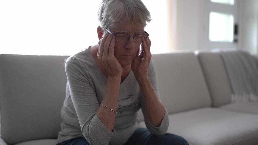 Unhappy headache Retired Senior Woman Sitting On Sofa At Home