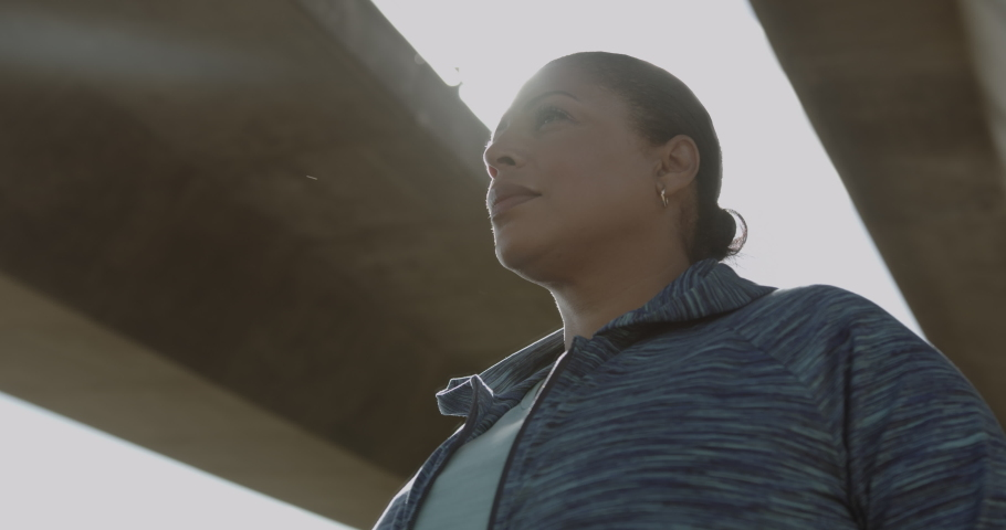 Portrait of Body positive Mature black female under bridge in city, Plus size obese overweight Latin American woman looking at camera Royalty-Free Stock Footage #1061271718