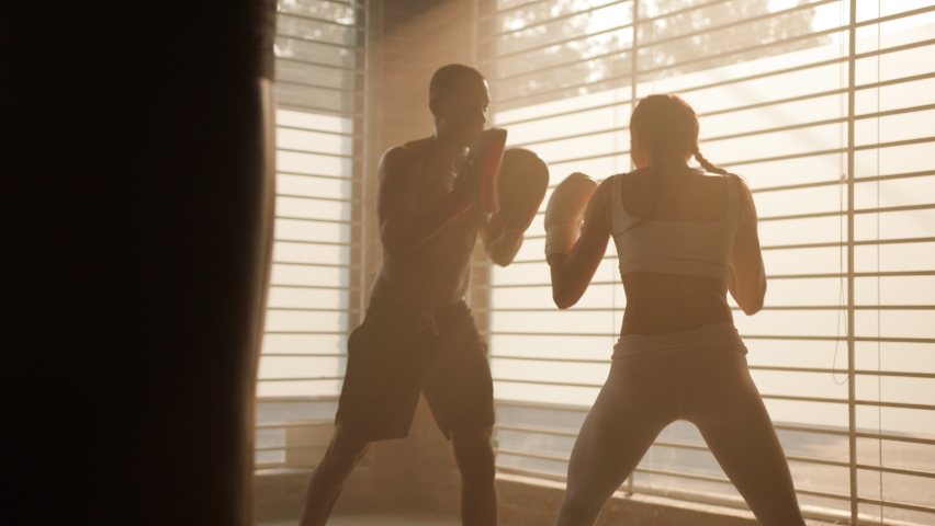 Boxing in urban gym / coach giving a Private training to a female athlete practicing a punch
