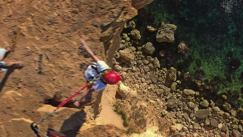Action shot of bungee jumping off a cliff onto a zipline over the sea. Royalty-Free Stock Footage #1061278030