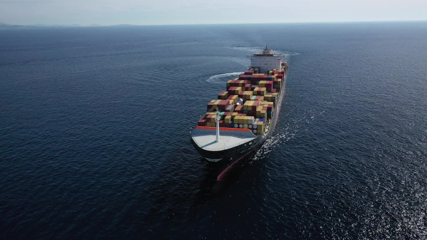 Aerial drone video of container ship with colourful truck size containers cruising in open ocean Mediterranean Aegean sea, Greece