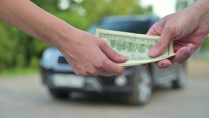 Car sale. A woman gives a man a key and takes money in return, selling him her car