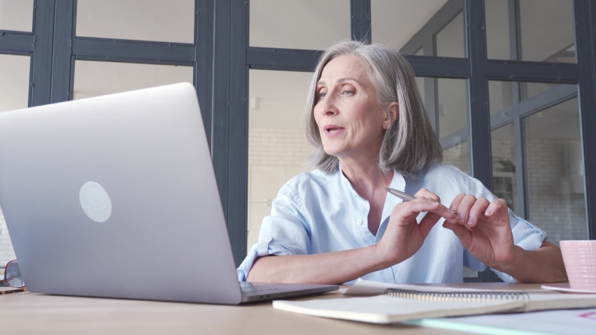 Middle aged business woman talking video conference calling on laptop. Senior old distance teacher communicating in online virtual chat remote meeting looking at computer working from home office. Royalty-Free Stock Footage #1061284720
