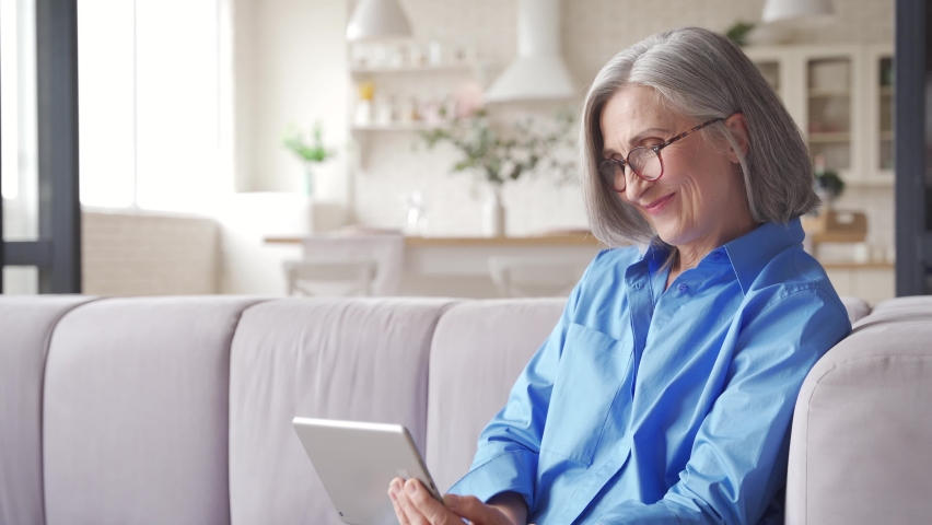 Happy old senior woman grandmother waving hand holding digital tablet video conference calling talking enjoying social distance party, virtual family online chat meeting with grandchildren at home.