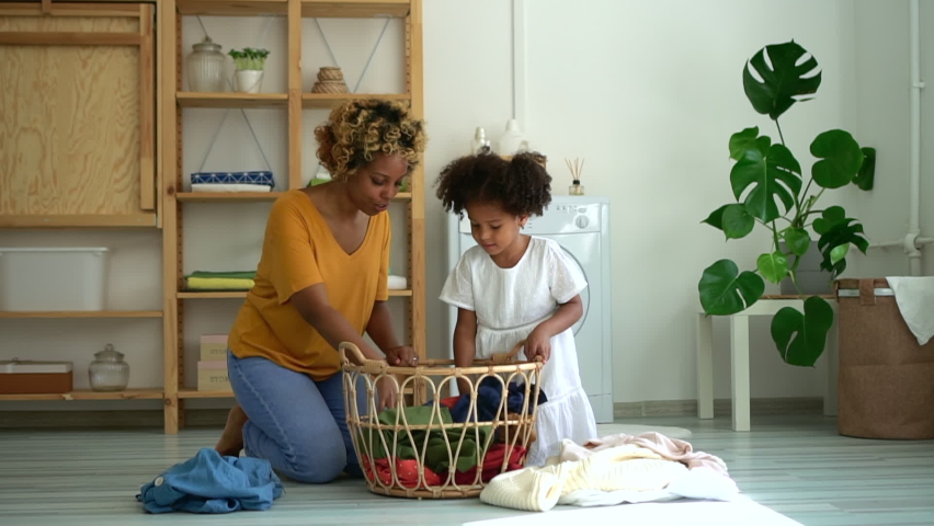 african mom and kid preparing clothes for laundry with washing machine together Spbd. housework, little girl help mom to wash dirty clothes in living room. Family, folding, basket concept Royalty-Free Stock Footage #1061285158