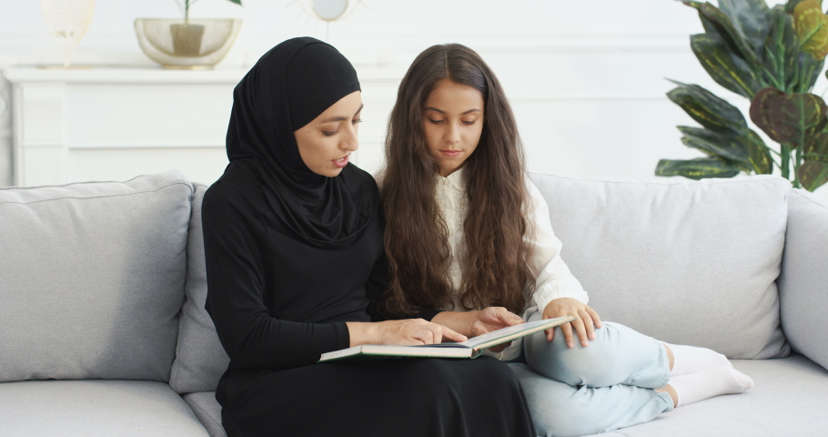 Young Arabic woman in black headscarf reading interesting story in book for pretty small teen girl. At home on sofa. Muslim mother learning and educating little teenage daughter with textbook. Royalty-Free Stock Footage #1061290582