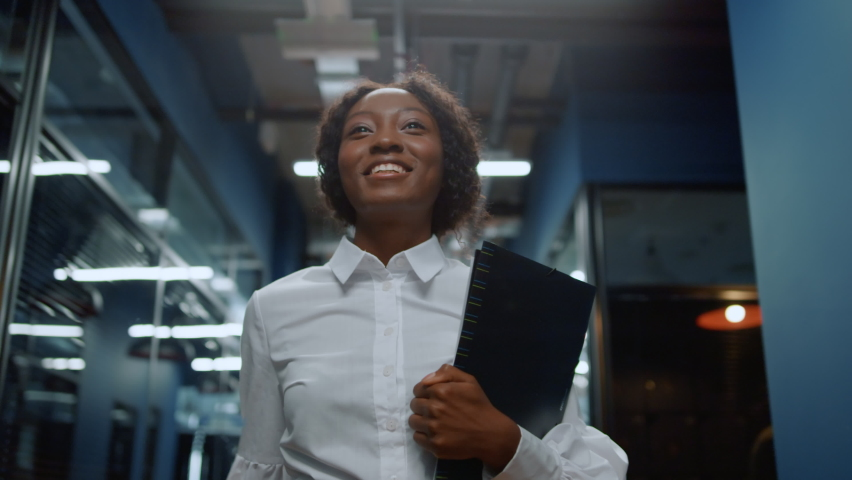 Smiling african business woman saying hi in office corridor. African american businesswoman greeting employee in corridor. Closeup beautiful afro woman waving hand in business center hallway Royalty-Free Stock Footage #1061295166