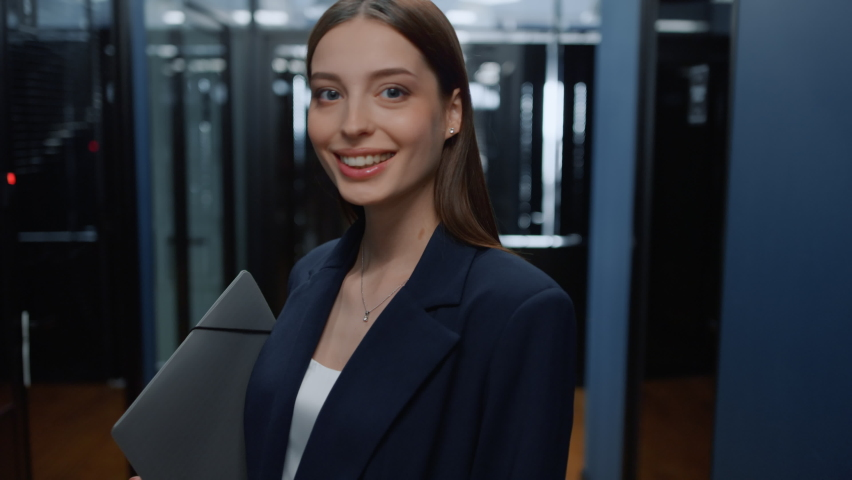 Portrait of smiling businesswoman posing in office corridor. Closeup charming female manager looking at camera in office hallway. Positive business woman holding folder in business center interior. | Shutterstock HD Video #1061295217