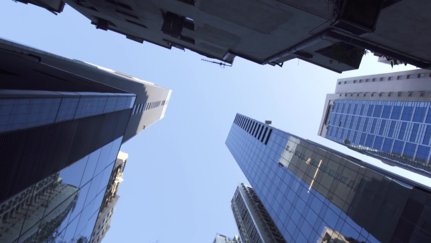 HONG KONG/CHINA - OCTOBER 15 2020: Turning among high office buildings with glass facades on downtown street of Chinese city under clear blue sky on sunny day low angle shot on October 15 in Hong Kong   Shutterstock HD Video #1061295748