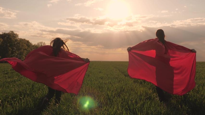 Happy girls play superheroes they run across green field in red cloak, cloak flutters in wind. children's games and dreams. Slow motion. teenager dreams of becoming superhero. young girls in red cloak | Shutterstock HD Video #1061295835