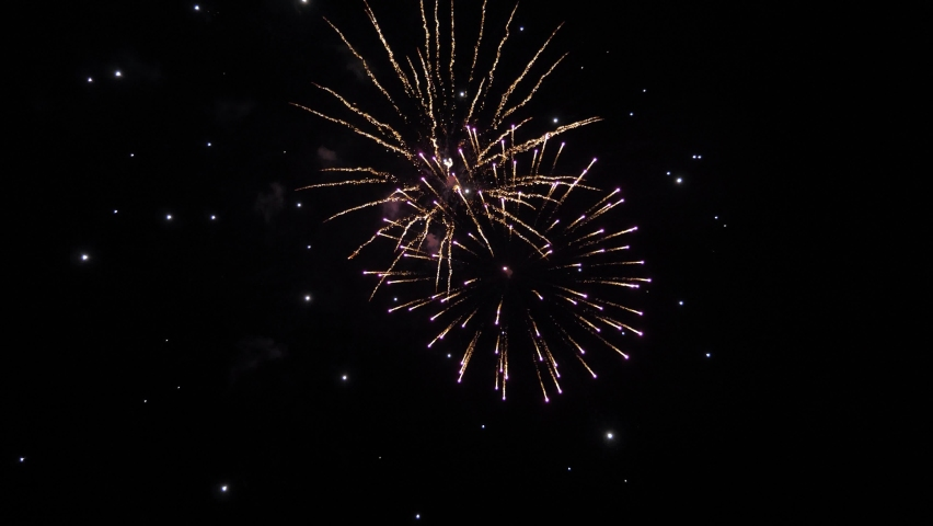 shining fireworks with bokeh lights in night sky. beautiful multi colored fireworks in night sky. New year's eve fireworks celebration. glowing fireworks show. colored night explosions in black sky Royalty-Free Stock Footage #1061295847