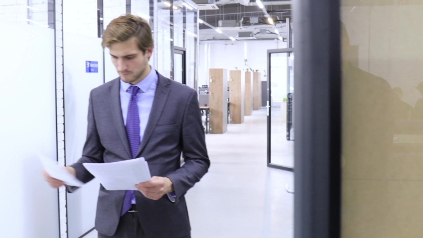 Serious businessman reading financial documents standing in the open space office hallway. | Shutterstock HD Video #1061305795