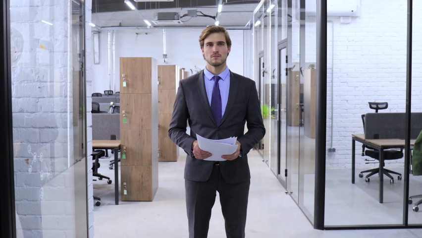 Serious businessman reading financial documents walking through the office. | Shutterstock HD Video #1061305801