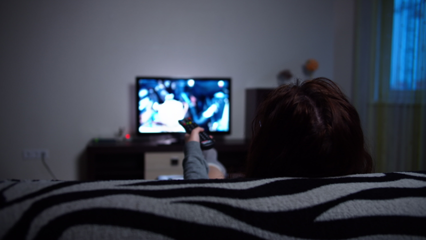 Woman relaxing at home on the sofa, switches tv channels in the evening, back view | Shutterstock HD Video #1061308342