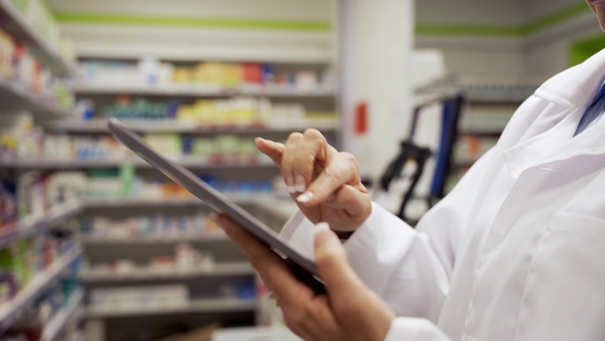 Close up of female pharmacist scrolling on digital tablet checking and counting stock of medicines on shelves in pharmacy  Royalty-Free Stock Footage #1061309434