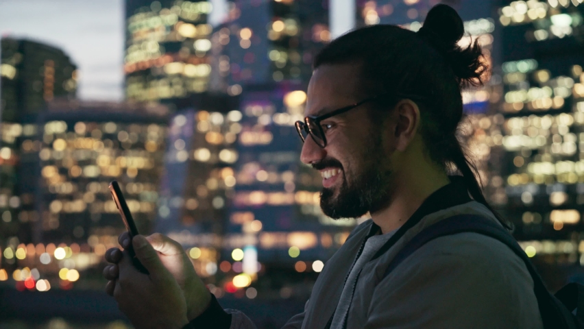 Handheld shot of a handsome bearded young man in glasses taking a video call with his smartphone on the street in the evening time. | Shutterstock HD Video #1061314909