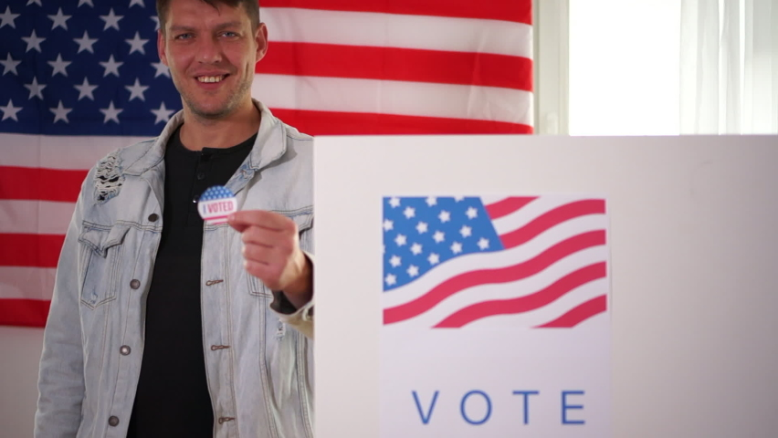 Young smiling American holds a vote sticker in front of a voting booth. The man is wearing a denim jacket. US elections concept