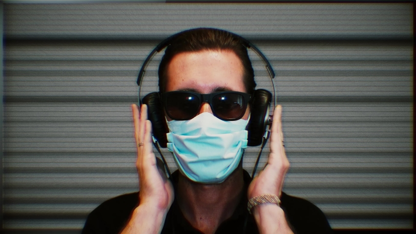 Isolated Man Face Mask Social Isolation, Alienation. Man wearing a face mask protection distracts himself listening to music. TV static background | Shutterstock HD Video #1061319079