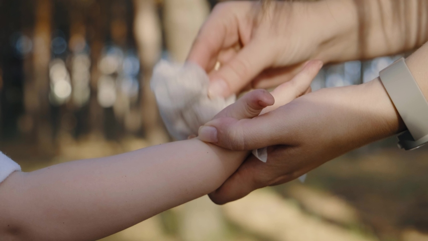 Child hands cleaning and disinfection. The mother wipes the child's hands with wet wipes in the park. | Shutterstock HD Video #1061319883