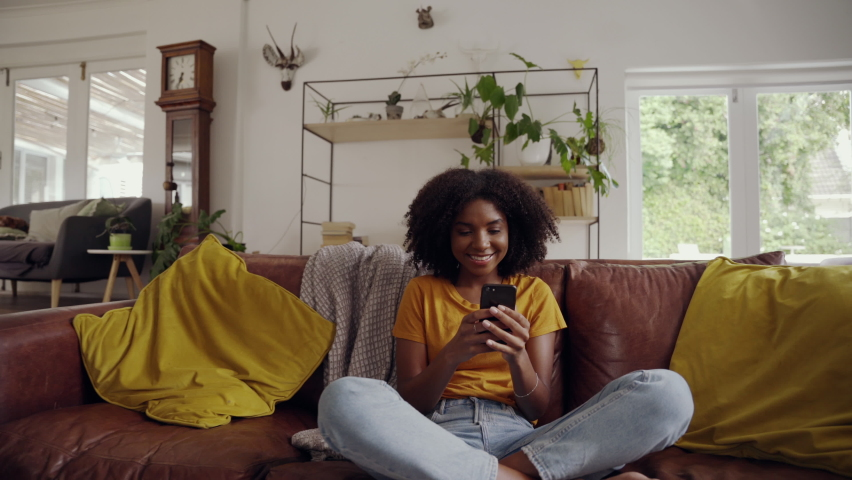 Smiling relaxed afro american woman sitting on sofa hold smart phone watching social media video in living room | Shutterstock HD Video #1061320651