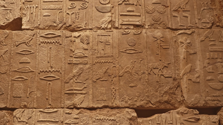 Background of antique stone wall with carved ancient Egyptian hieroglyphs, close up, pan front view