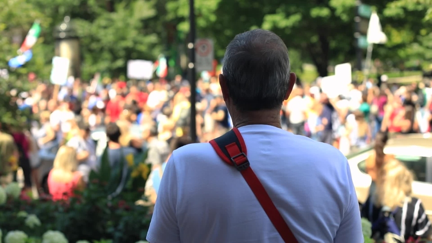 Selective focus rear view of adult male standing far away from the crowd looking at unrecognized people revolting march against fake news | Shutterstock HD Video #1061323000
