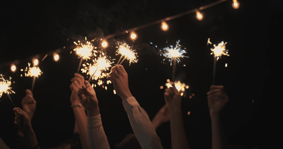 Hands in the dark waving sparklers . on backdrop of garland. new year, holiday, Christmas, birthday, party. Cheerful Partying With Sparkler Fire Smiling . Night Shot | Shutterstock HD Video #1061327077