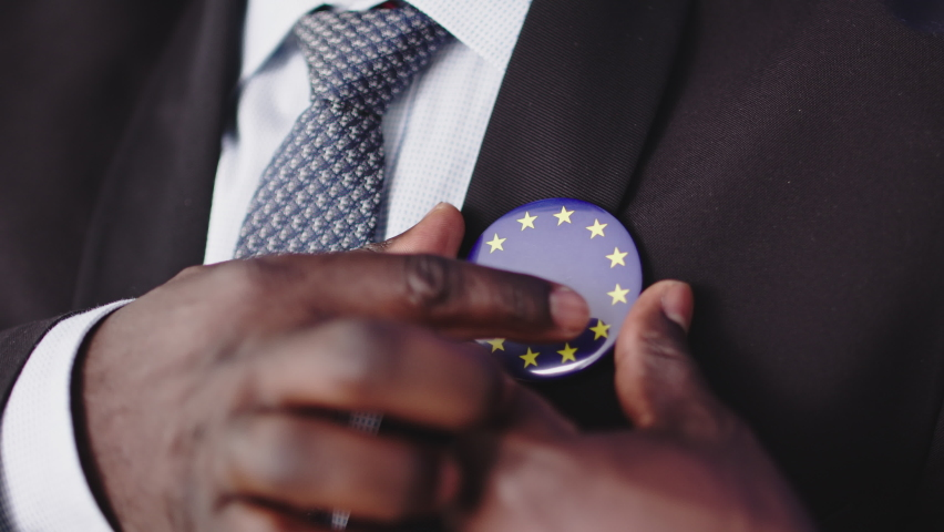 A Circular European Flag Enamel Pin Badge Brooch Worn By A Man On A Black Suit With Blue Tie. - close up shot