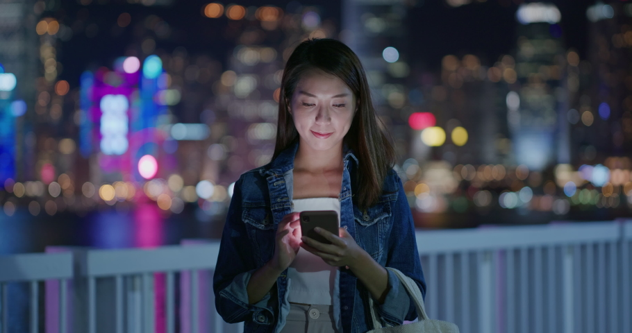 Woman check on smart phone in city at night   Shutterstock HD Video #1061333785