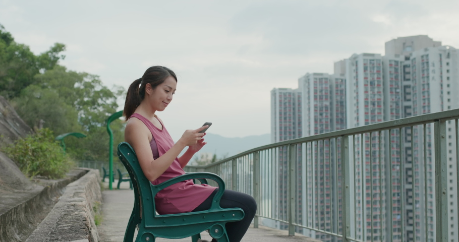 Woman use of mobile phone and sit at wooden bench   Shutterstock HD Video #1061333794