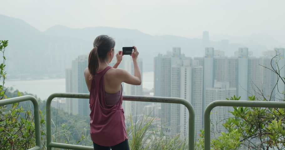Woman use of mobile phone to take photo in city   Shutterstock HD Video #1061333800